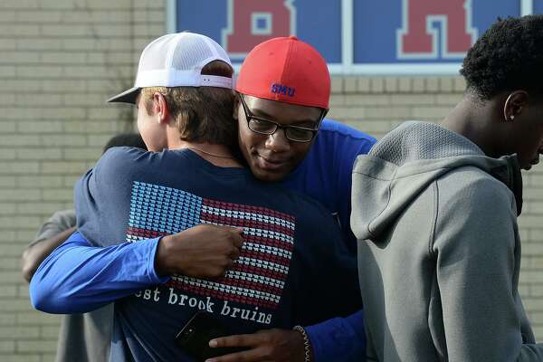 Braden Sheldon embraces Jay Bell during Sunday's prayer service for the four West Brook football players injured in a car wreck this weekend. Photo taken Sunday, 7/14/19