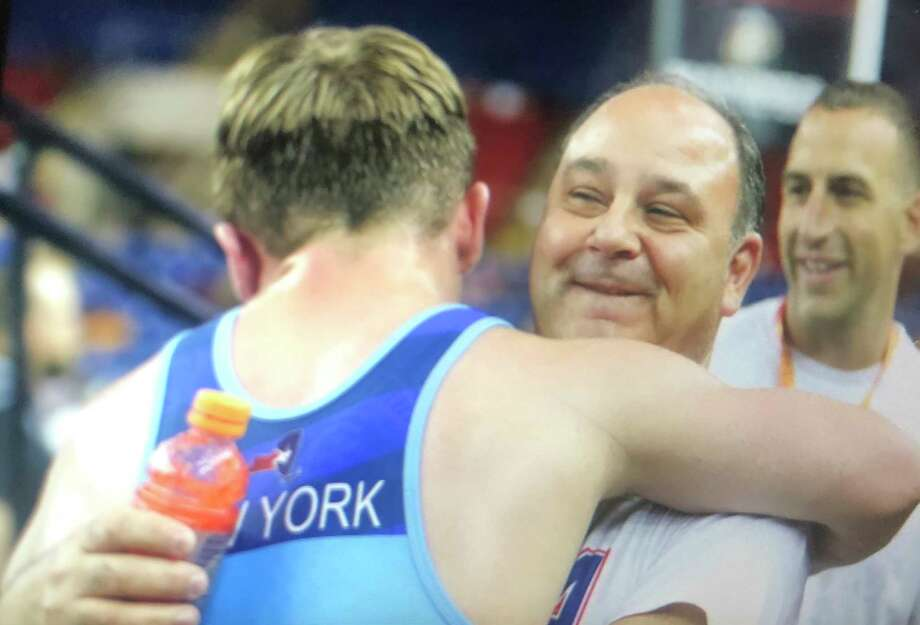 Columbiaa€™s Michael Altomer shares an embrace with his coach Anthony Servidone following his quarterfinal win at the Junior Nationals.