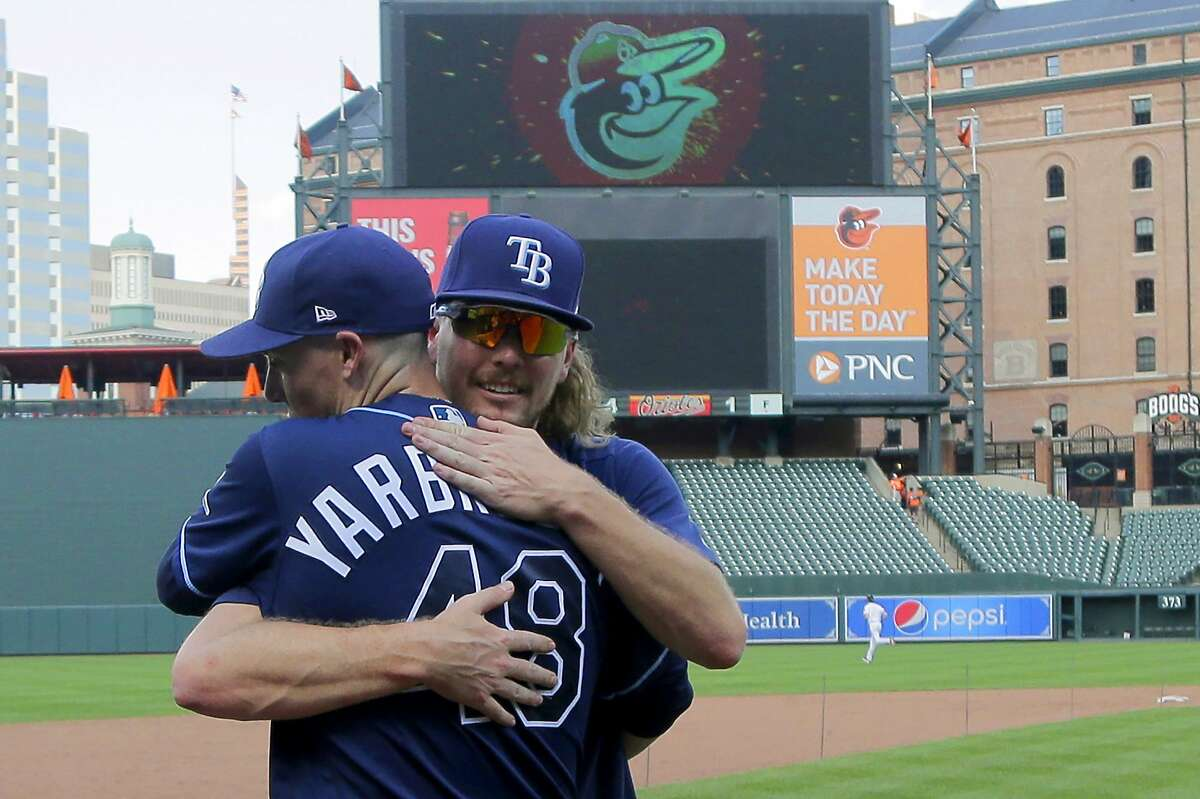 Tampa Bay Rays pitchers Ryan Yarbrough (48) and Ryne Stanek embrace after giving an interview after a baseball game against the Baltimore Orioles, Sunday, July 14, 2019, in Baltimore. The two pitchers had a combined perfect game through eight innings, until Orioles' Hanser Alberto hit a single on Yarbrough's first pitch in the ninth. (AP Photo/Julio Cortez)