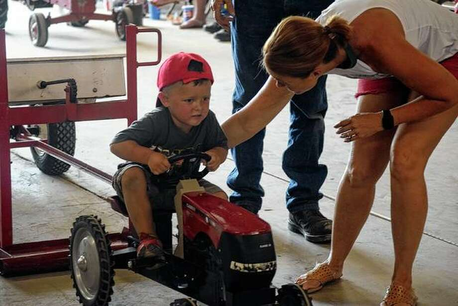 Landon Ward, 3, the son of Keith and Alison Ward of Jacksonville competes in the pedal tractor competition Sunday at the Morgan County Fair. Photo: Samantha McDaniel-Ogletree | Journal-Courier