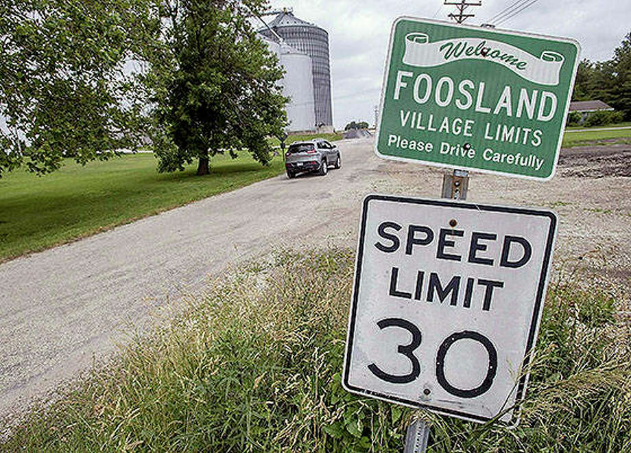 A car drives past signs near the south edge of Foosland. Photo: Rick Danzl | News-Gazette (AP)