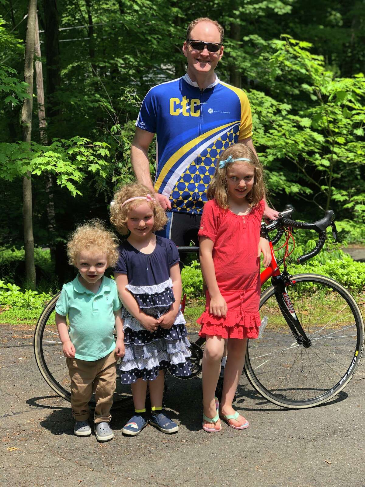 Ridgefielder Paul Fitzpatrick with his three children. On July 27, he willcycle 100 miles to raise$10,000 for the CT Challenge -a nonprofit organization dedicated to helping the 15.5 million cancer survivors in Connecticut and throughout the U.S.