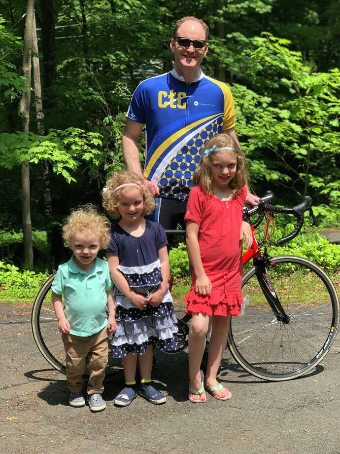 Ridgefielder Paul Fitzpatrick with his three children. On July 27, he will cycle 100 miles to raise $10,000 for the CT Challenge —  a nonprofit organization dedicated to helping the 15.5 million cancer survivors in Connecticut and throughout the U.S. Photo: Kate Fitzpatrick / Contributed Photo