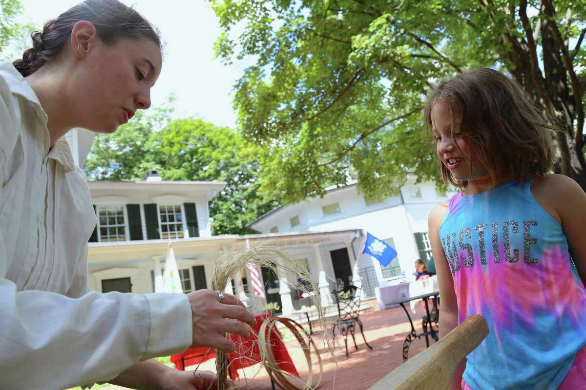 Nicole Carpenter, director of programs & education, shows Audrey Swanson, 8, of Westport, some techniques for making thread at the Westport Historical Society's family day event commemorating the 1779 burning of Greens Farms, on Saturday, July 13, 2019, in Westport, Conn.