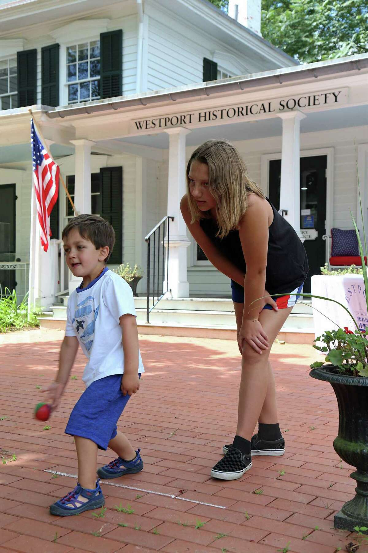 William Duffy, 4, of Colorado Springs, Colorado, and his sister, Bridget, 11, play a game at the Westport Historical Society's family day event commemorating the 1779 burning of Greens Farms, on Saturday, July 13, 2019, in Westport, Conn.