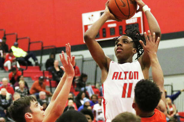 Alton's Donovan Clay (11) rises up in the lane for a shot over Edwardsville defenders during the Redbirds' Southwestern Conference victory at Alton High in Godfrey.