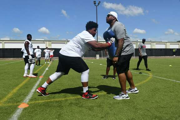 Youth camp participant Deossieion Yancey, 14, left, a freshman at St. John's XXIII Catholic School, works on his blocking technique with camp host Kevin Vickerson during his B.GR8 Lineman Camp for Houston youth football players at Ollin Athletics and Sports Medicine in Cypress on July 13, 2019.