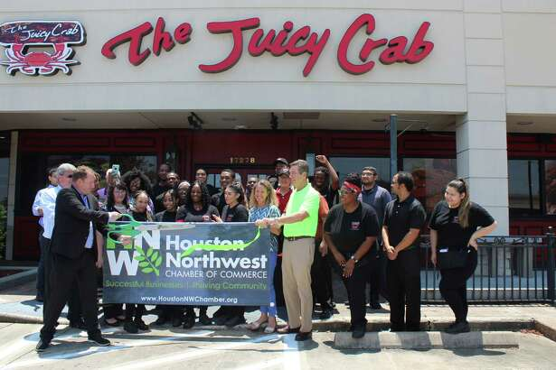 Todd Strickland, director of marketing and franchise sales for The Juicy Crab, cuts the ribbon on The Juicy Crab's first Texas location in Houston during a grand opening celebration on July 11.