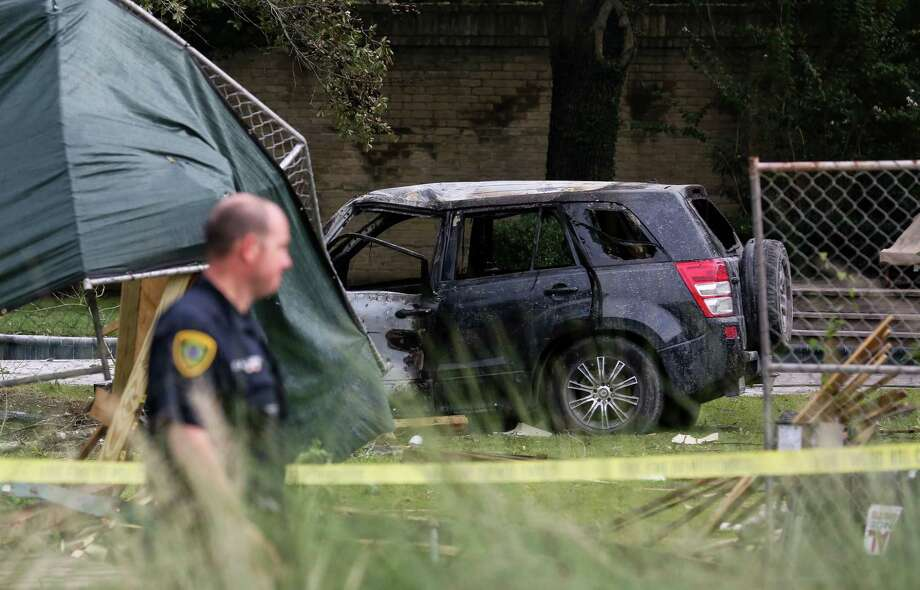 The Houston Police Department investigates the scene where a suspect crashed into the backyard of a residence on South Piney Point Road near Woodway Drive Monday, July 15, 2019, in Houston. The vehicle caught fire after the crash. Photo: Godofredo A. Vásquez, Staff Photographer / 2019 Houston Chronicle