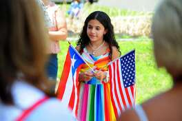Juiliana Spinelli, 9, holds Puerto Rican and American flags during a Puerto Rican Flag raising ceremony at Bridgeport City Hall in Bridgeport, Conn., on Saturday July 13, 2019. The Peurto Rican Parade of Fairfield County takes place Sunday, beginning at 11 a.m. at Central High School and concludes with an all day celebration at Seaside Park.