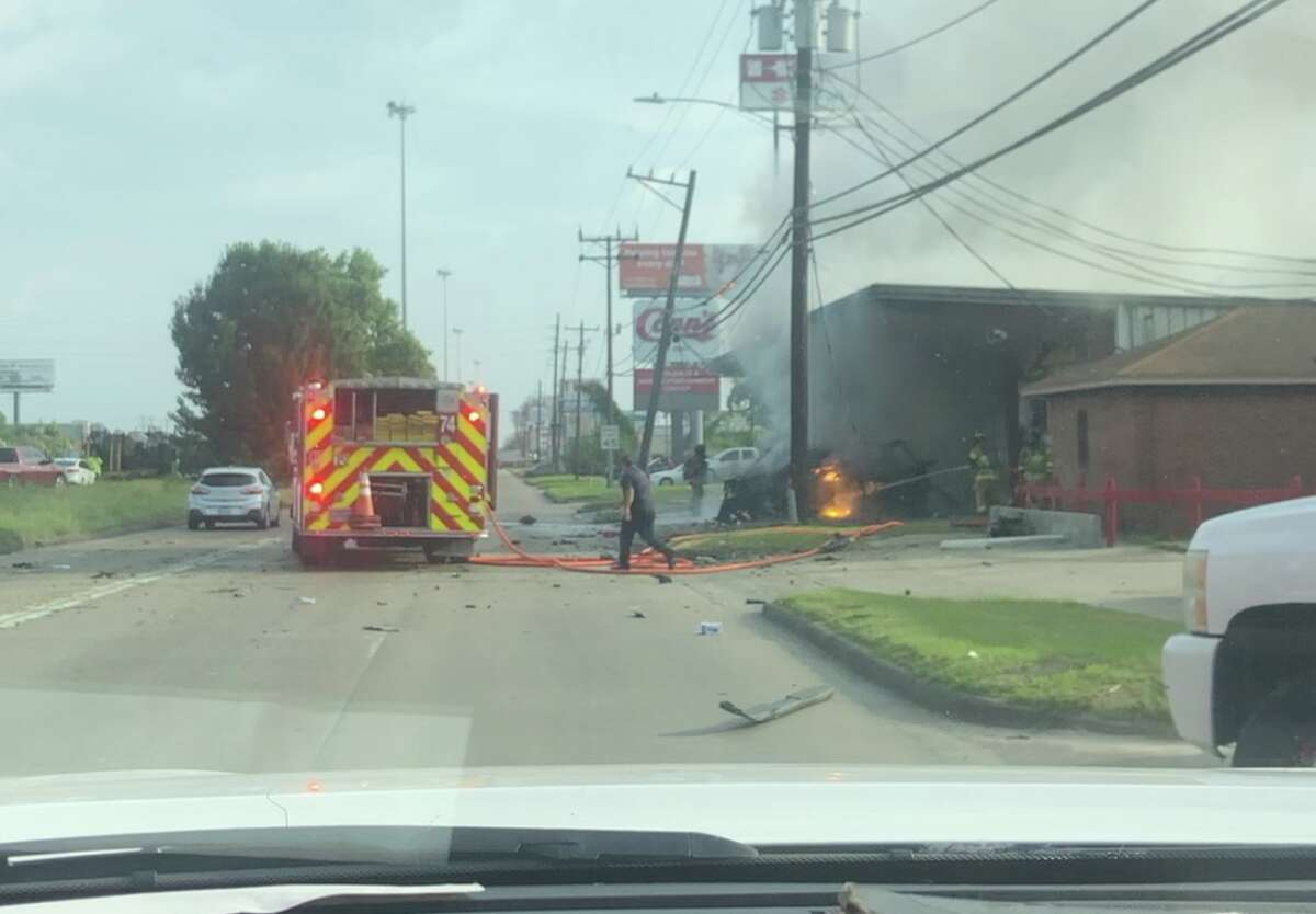 A pickup truck involved in a deadly crash is seen burning after the driver crashed into a north Houston motorcycle shop Monday, July 15, 2019.