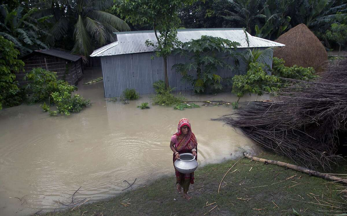 A flood affected woman carries drinking water on an embankment in Pabhokathi village east of Gauhati India, Monday, July 15, 2019. After causing flooding and landslides in Nepal, three rivers are overflowing in northeastern India and submerging parts of the region, affecting the lives of more than 2 million, officials said Monday.(AP Photo/Anupam Nath)