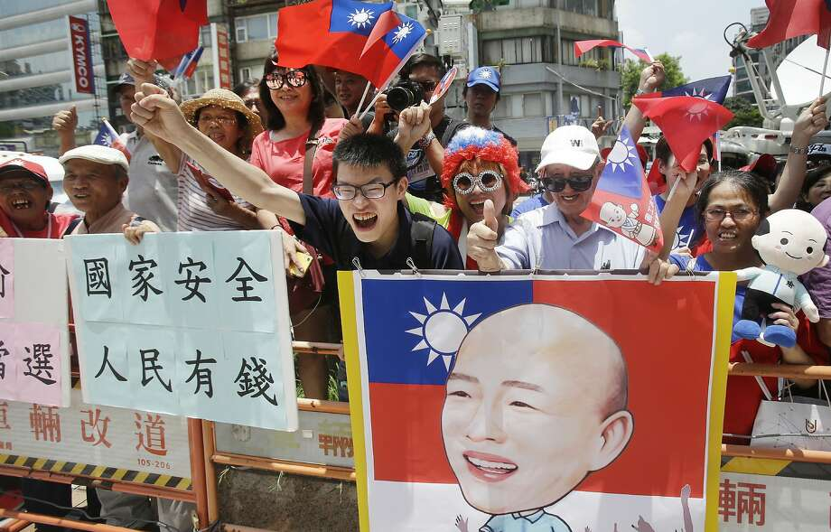 """Supporters of the pro-China Kaohsiung city mayor Han Kuo-yu celebrate after he won the candidacy of the opposition of the Nationalist Party (KMT) for the upcoming presidential elections at the party headquarters, Monday, July 15, 2019, in Taipei, Taiwan. The placard reads """"Nation safe, people rich!"""" (AP Photo/Chiang Ying-ying) Photo: Chiang Ying-ying / Associated Press"""
