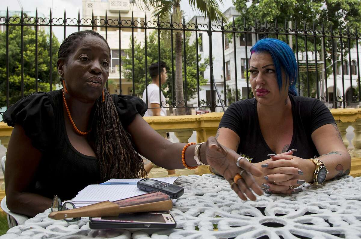 In this June 28, 2019, photo, Dianelys Alfonso, right, singer, sits with her lawyer Deyni Terry, for a photo during an interview with The Associated Press in Havana, Cuba. Alfonso publicly denounced another renowned musician, flutist and bandleader Jos� Luis Cort�s, accusing him of repeatedly hitting and raping her during her time as vocalist for NG La Banda. Terry said she and her client are still investigating whether they can bring charges of abuse and sexual assault against Cort�s many years after the alleged crimes took place. (AP Photo/Ismael Francisco)