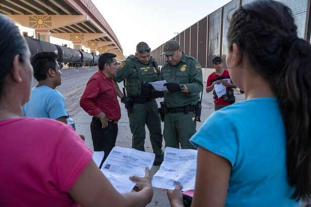 (FILES) In this file photo taken on May 16, 2019 US Customs and Border Protection agents check documents of a small group of migrants, who crossed the Rio Grande from Juarez, Mexico in El Paso, Texas. - The Trump administration moved on July 15, 2019 to block most migrants who cross the US southern border after passing through Mexico from seeking asylum.A new rule redefining asylum eligibility -- to take effect on Tuesday -- is the latest attempt to stem the flow of undocumented migrants into the country, and comes amid White House frustration at Congress's failure to change asylum laws. (Photo by Paul Ratje / AFP)PAUL RATJE/AFP/Getty Images