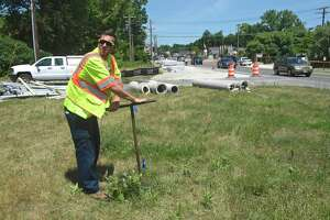"""Grant Daniels, from Aquarion Water Company, turns the water back on to a section of a 12"""" water main that was damaged Monday morning after repairs were completed. An excavator working on the streetscape project in the Four Corners section of Brookfield poked a hole in the water main. Monday, July 15, 2019, in Brookfield, Conn."""