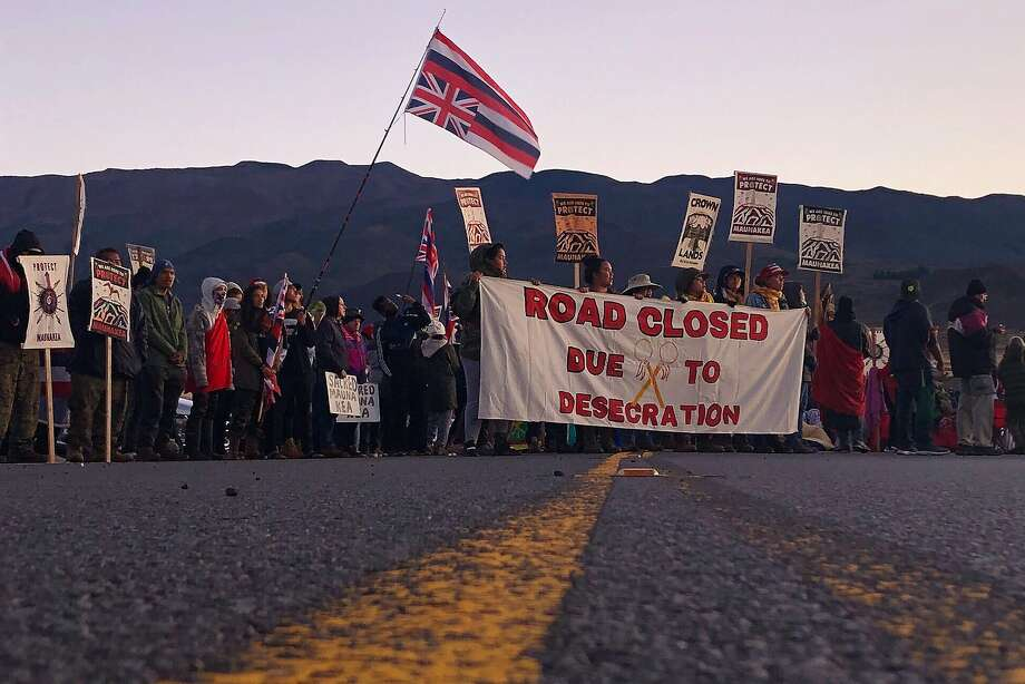 Demonstrators are gather to block a road at the base of Hawaii's tallest mountain, Monday, July 15, 2019, in Mauna Kea, Hawaii, to protest the construction of a giant telescope on land that some Native Hawaiians consider sacred. (AP Photo/Caleb Jones) Photo: Caleb Jones / Associated Press