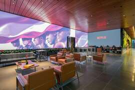 """The showpiece of Netflix's lobby, an 80-foot by 12-foot video screen, in Los Angeles, June 26, 2019. Every day an entertainment's who's who passes through the lobby, a 4,780-square-foot """"creative gateway,"""" hoping for a piece of the billions Netflix is spending on content. (Hunter Kerhart/The New York Times)"""