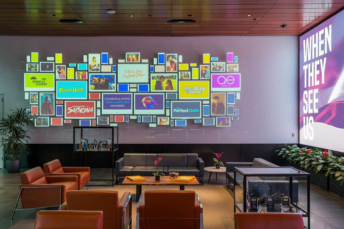 """A wall in Netflix's lobby features displays of some of the streaming service's shows and stars, in Los Angeles, June 26, 2019. Every day an entertainment's who's who passes through the lobby, a 4,780-square-foot """"creative gateway"""" - complete with an 80-foot video screen - hoping for a piece of the billions Netflix is spending on content. (Hunter Kerhart/The New York Times)"""