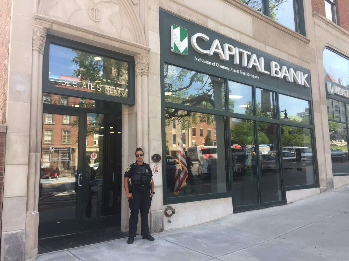 An Albany police officer stands outside Capital Bank on State Street in Albany, N.Y., on Monday, July 16, 2019, after the bank was robbed.