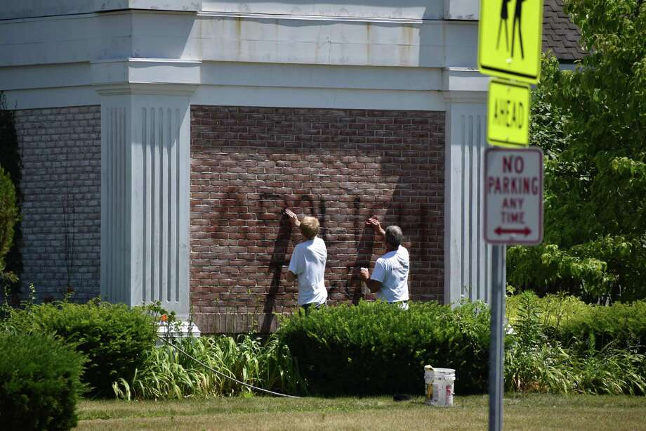 Men removing vandalism outside Saint Joseph Catholic Church on Whisconier Road on July 15, 2019. Photo: Kendra Baker / Hearst Connecticut Media