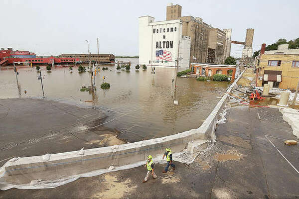The portion of downtown Alton near the intersection of East Broadway and Piasa Street was a flooded mess Monday, June 3. The city flood wall kept a the majority of water from reaching downtown bussinesses. Illinois is now tallying damages from spring flooding to see if it totals $19 million to trigger federal assistance.