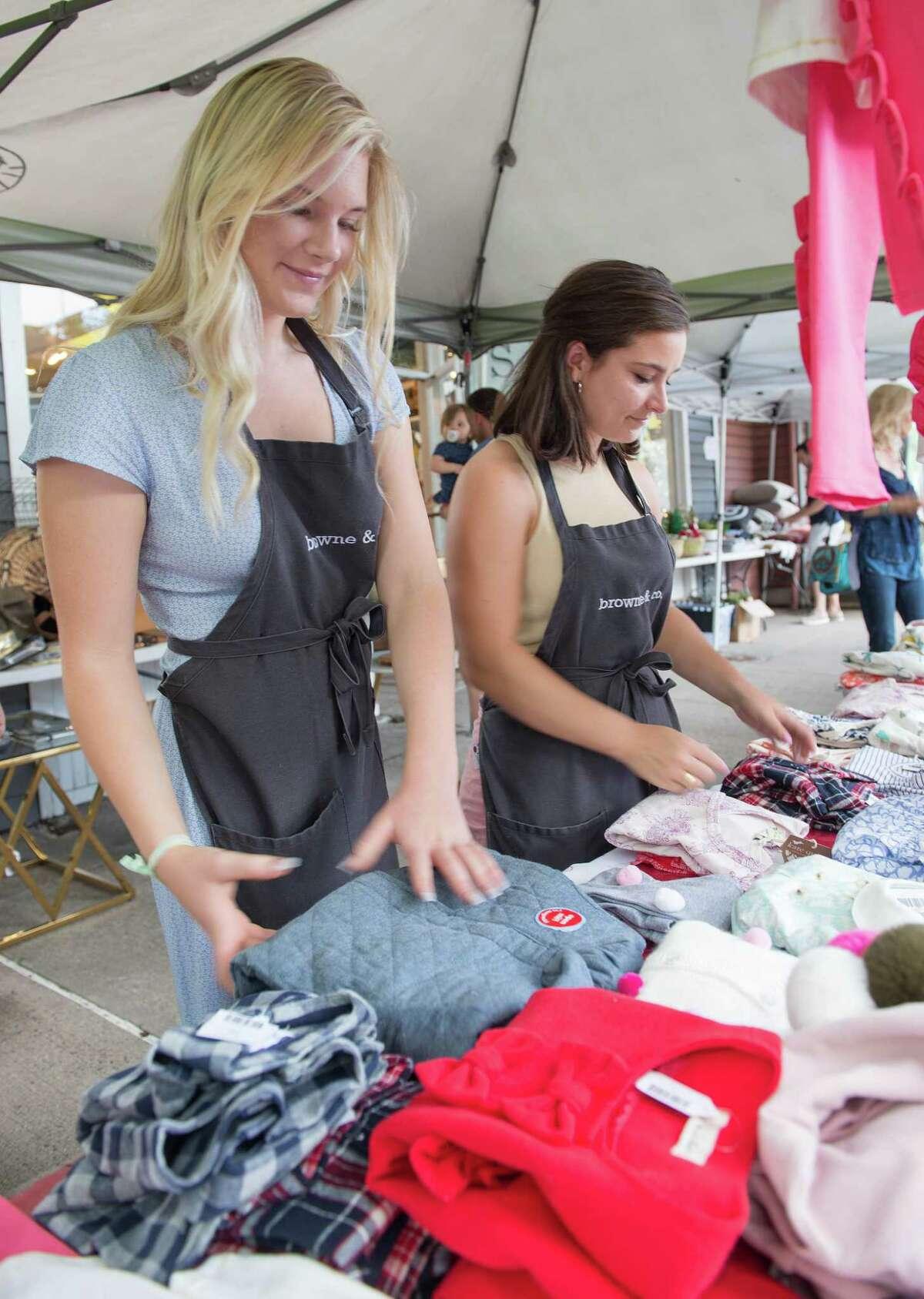 Graylin Gogolak and Katie Lashendock arrange shirts at Browne & Company at the Darien Sidewalk Sales on Friday, July 12, 2019 in Darien, Connecticut.