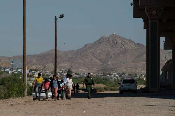 After crossing the Rio Grande from Mexico into the United States, migrants walk between Border Patrol agents in El Paso on June 13. Crossings into the United States dropped precipitously from May to June.