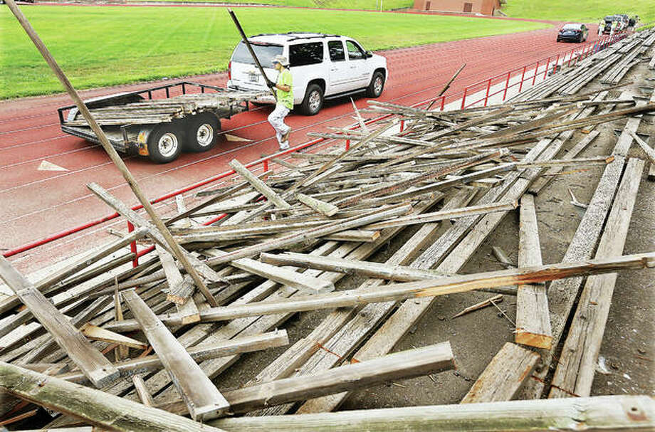 A construction worker on Monday stacks 2-by-4-inch boards removed from the visitors side bleachers in Alton's Public School Stadium. The previous bleachers, on both sides of the football field, were wood and covered with a vinyl-type of outer skin to make them smoother. The former red, white and blue bleachers are being replaced with a new aluminum seated structure.