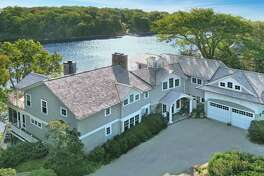 The colonial house at 9 Stony Point Road in the private Stony Point Association sits high above the Saugatuck River with direct frontage, views, and water access.