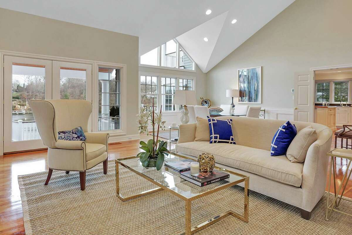 The spacious, two-story formal living room features a marble fireplace, built-in cabinetry and shelving, an interior balcony, vaulted ceiling, and French doors to the large open, tiered deck.