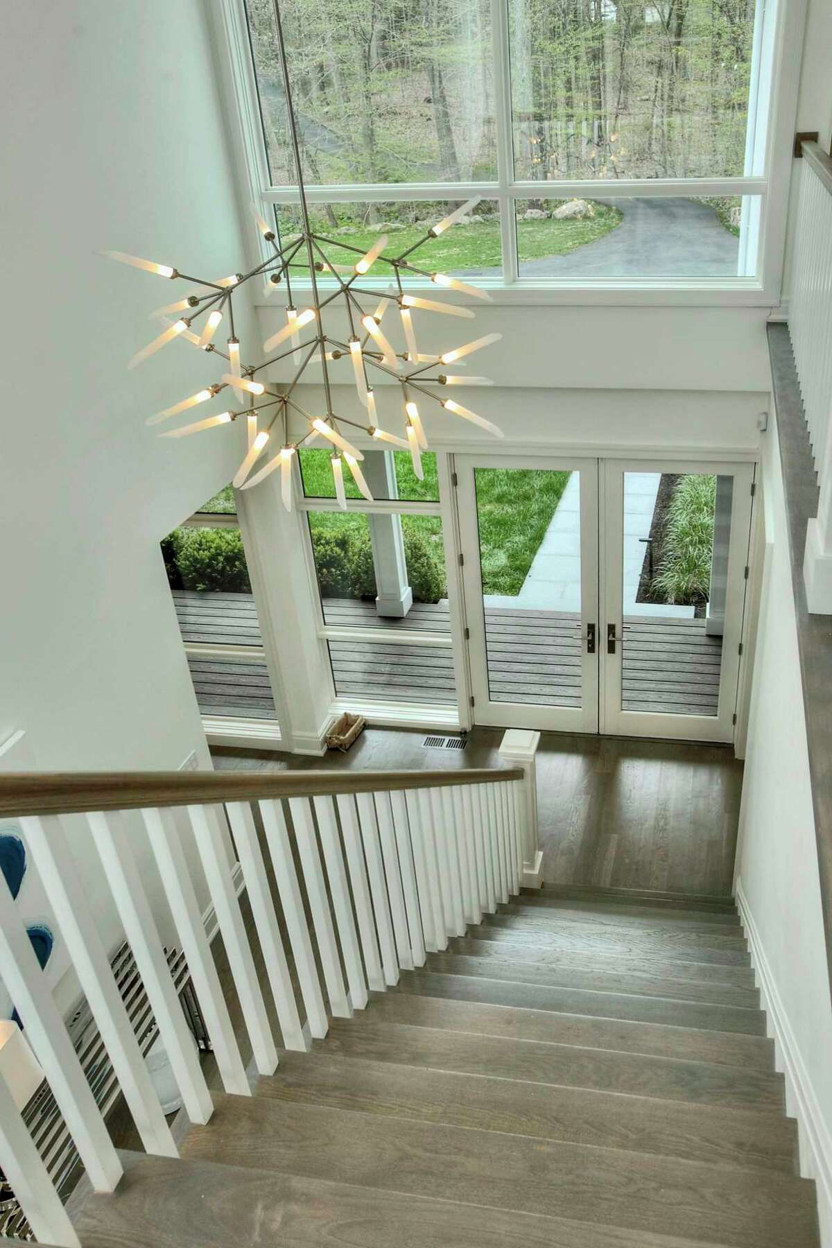 The striking center hall two-story foyer has an open staircase and an intriguing light fixture.