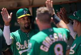 OAKLAND, CA - JULY 13:  Marcus Semien #10 of the Oakland Athletics is congratulated by teammates after he scored against the Chicago White Sox in the bottom of the first inning at Ring Central Coliseum on July 13, 2019 in Oakland, California.  (Photo by Thearon W. Henderson/Getty Images)