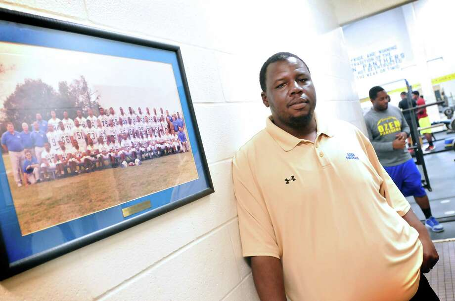 Ozen football coach Ed Taylor stands beside a portrait of the 1998 Panthers, the first team to partcipate in varsity football in the school's history. Taylor, a 2000 Ozen graduate, was a part of the team as a junior. Mike Tobias/The Enterprise