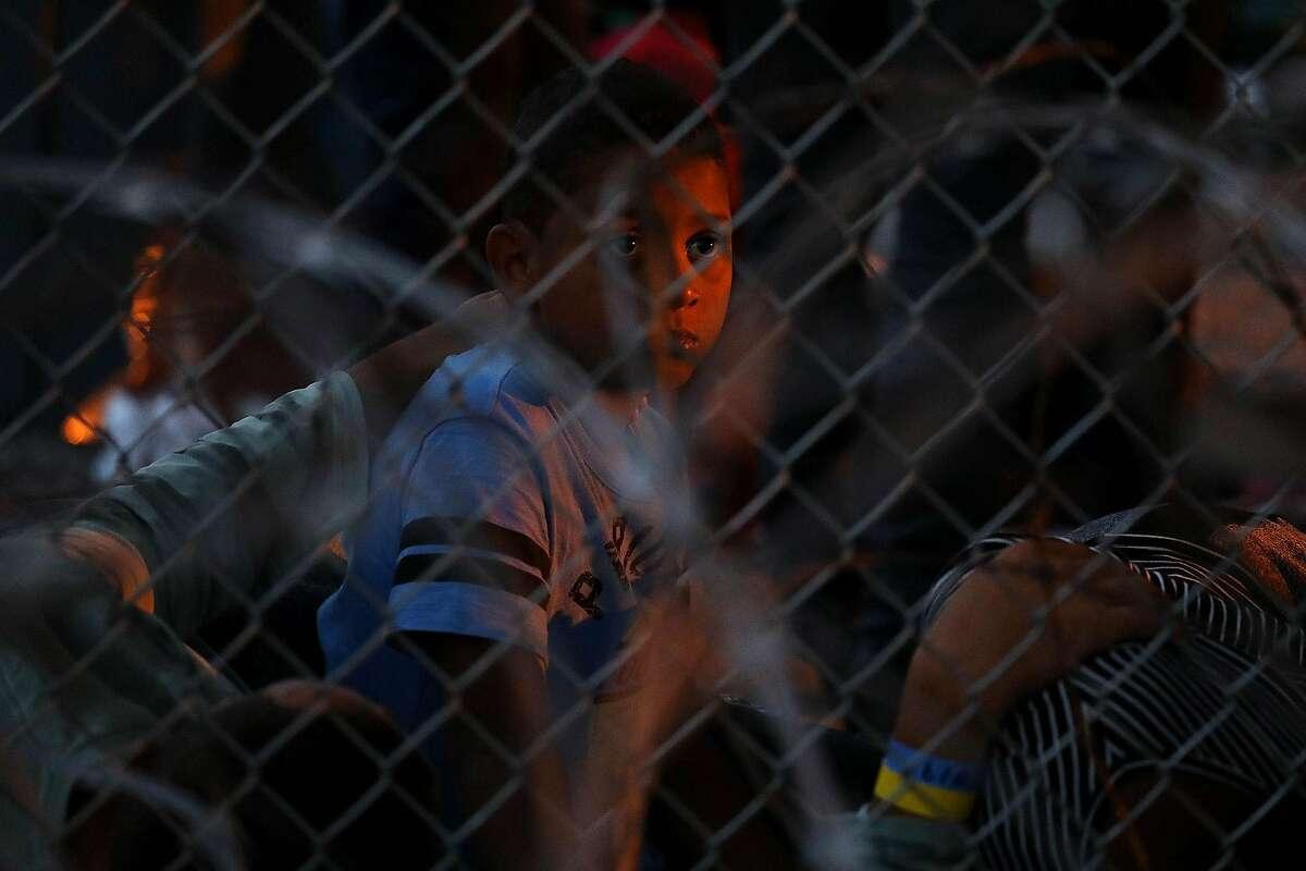 Migrants seeking asylum, including children, are held in a temporary transition area under the Paso Del Norte bridge in El Paso, Texas, in March 2019. (Gary Coronado/Los Angeles Times/TNS)