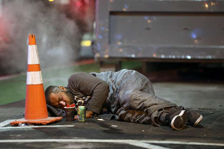 (3:53 a.m.) A man rests on the street at the intersection of Market St. and 2nd St. in San Francisco on Wednesday, June 19, 2019. Photo: Guy Wathen / The Chronicle