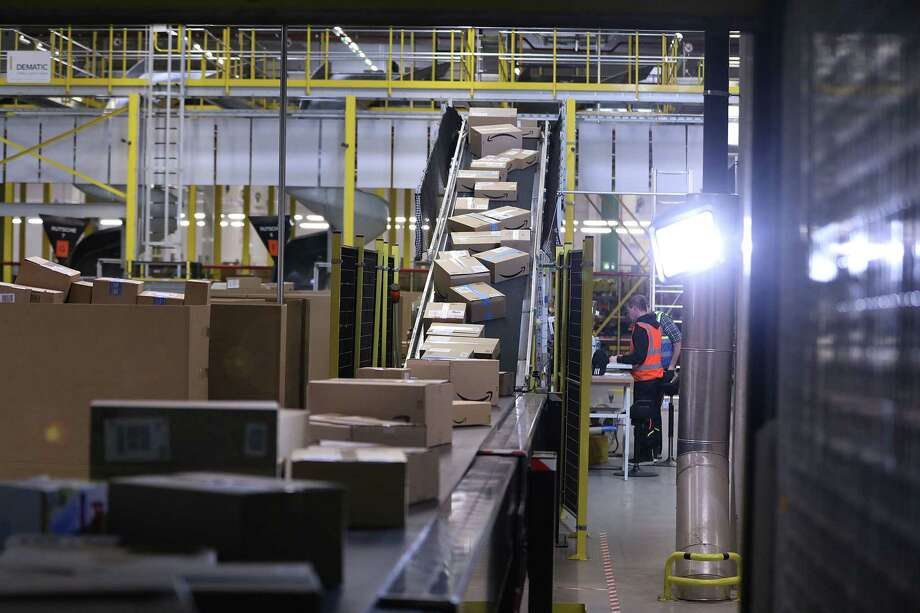 Amazon packages flow through a conveyor belt in a warehouse. Photo: Bloomberg Photo By Krisztian Bocsi. / © 2019 Bloomberg Finance LP