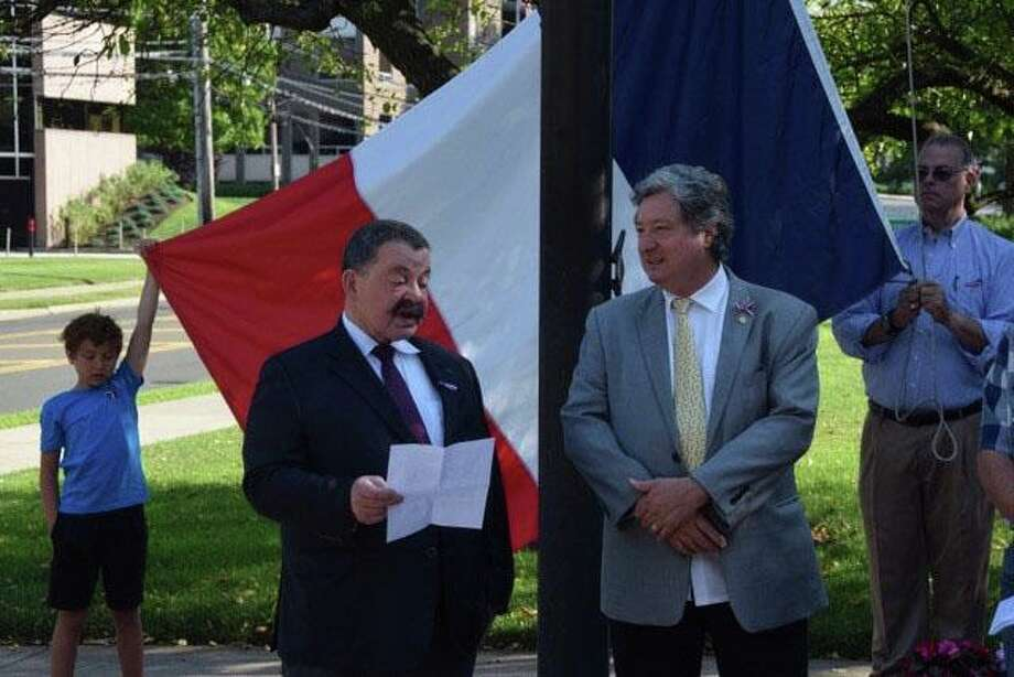 Mathew Chardain and Justin Can Ingen hold the French flag behind Jean Lachaud and Master of Ceremonies Jean-Louis Gerin during the Bastille Day celebration hosted by the Alliance Francaise of Greenwich held Sunday in front of town hall. The ceremony was followed by a lunch at L'Escale, an up-scale French restaurant off the Greenwich harbor. Photo: Anne Friday / Contributed