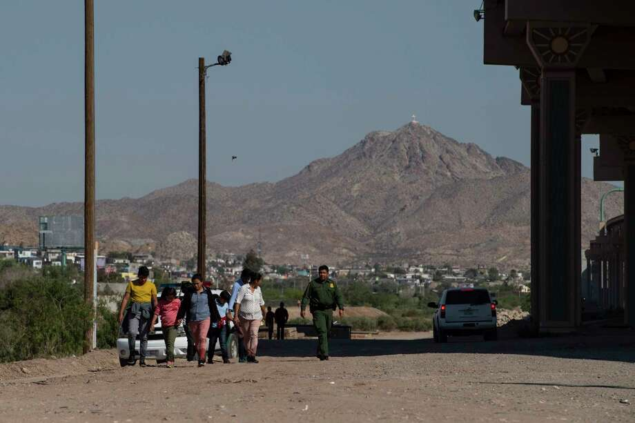 After crossing the Rio Grande from Mexico into the United States, migrants walk between Border Patrol agents in El Paso on June 13. Crossings into the United States dropped precipitously from May to June. Photo: Washington Post Photo By Carolyn Van Houten / The Washington Post