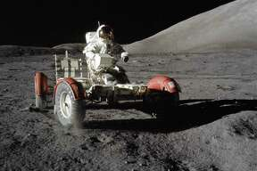 """Astronaut Eugene A. Cernan, commander, makes a short checkout of the Lunar Roving Vehicle (LRV) on Dec. 11, 1972 during the early part of the first Apollo 17 extravehicular activity at the Taurus-Littrow landing site. This view of the """"stripped down"""" rover is prior to loading up. Equipment later loaded onto the rover included the ground-controlled television assembly, the lunar communications relay unit, hi-gain antenna, low-gain antenna, aft tool pallet, lunar tools and scientific gear. This photograph was taken by scientist-astronaut Harrison H. Schmitt, lunar module pilot. The mountain in the right background is the east end of South Massif. While astronauts Cernan and Schmitt descended in the Lunar Module """"Challenger"""" to explore the moon, astronaut Ronald E. Evans, command module pilot, remained with the Command and Service Module in lunar orbit."""