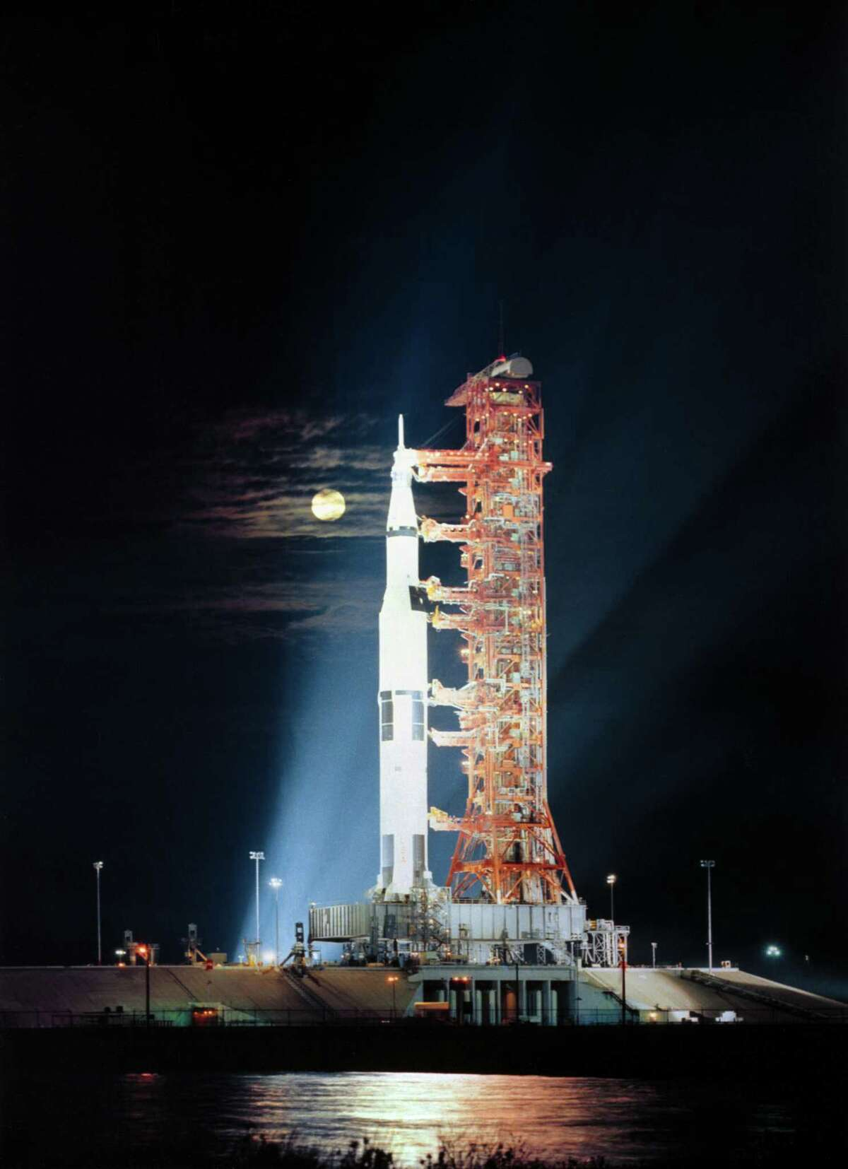Searchlights illuminate the nighttime scene in November 1972 at the Kennedy Space Center in Florida, showing the Apollo 17 spacecraft during prelaunch preparations. Apollo 17, the final lunar landing mission in NASA's Apollo program, was the first nighttime liftoff of the huge Saturn V launch vehicle. Apollo 17 launched Dec. 7, 1972 with astronaut Gene Cernan, commander; Ronald Evans, command module pilot; and scientist-astronaut Harrison H. Schmitt, lunar module pilot. The full moon can be seen in the background.