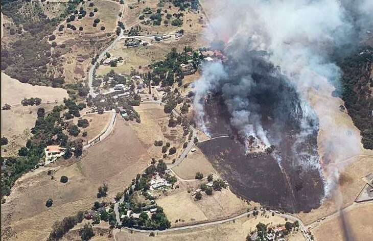 A brush fire broke out in East San Jose on Monday, July 15, 2019 threatening nearby structures, authorities said.