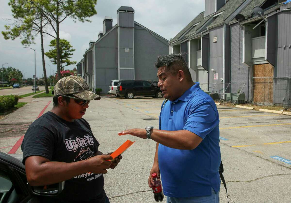 """FIEL organizer Alain Cisneros, right, hands out a """"Know Your Rights"""" pamphlet to a man outside the El Paraiso Apartments complex Monday, July 15, 2019, in Houston. ICE agents conducted a raid at the complex early Monday morning."""