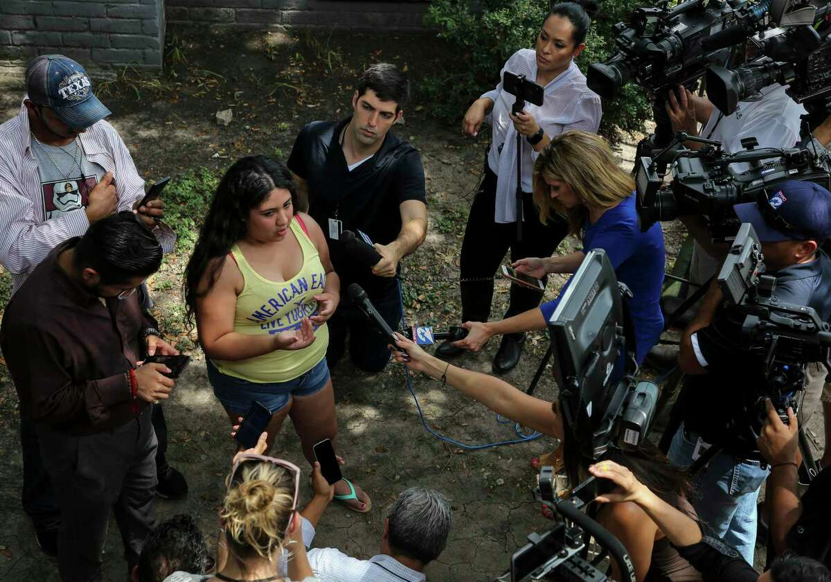 Kaylin Garcia, center, talks to reporters about the raid conducted by ICE agents early morning at the El Paraiso Apartments complex Monday, July 15, 2019, in Houston. She took a photograph of the agents at the complex and posted on social media.