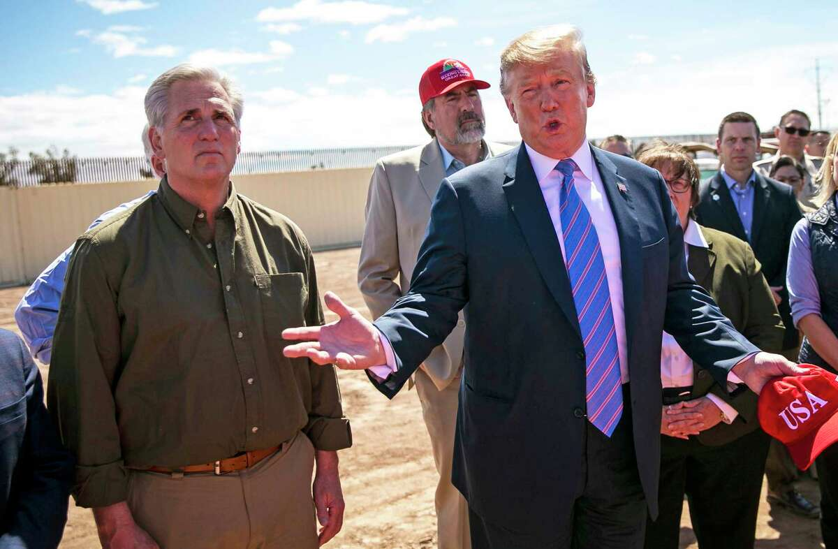 """President Donald Trump, right, speaks while visiting members of Border Patrol inspect newly upgraded border fencing as House Minority Leader Kevin McCarthy (R-Calif.), left, listens on in Calexico, California on Friday, April 5, 2019. None of California's seven GOP House members, including McCarthy, addressed the tweets Trump posted on Sunday that certain Democratic congresswomen """"originally came from countries whose governments are a complete and total catastrophe"""" and that they should """"go back and help fix the totally broken and crime infested places from which they came."""""""