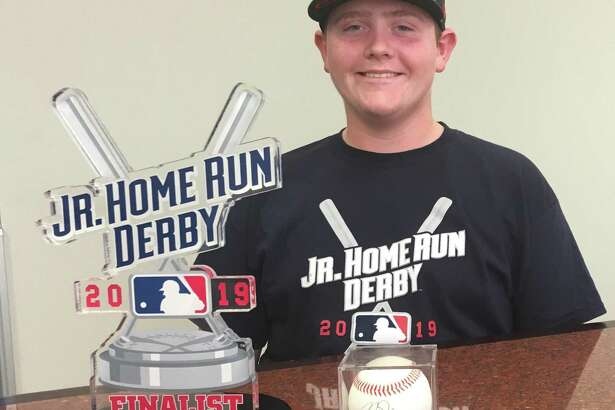 Conroe student Karsen Luther poses with his MLB Jr. Home Run Derby finalist trophy along with an autographed baseball from Los Angeles Angels outfielder Mike Trout.