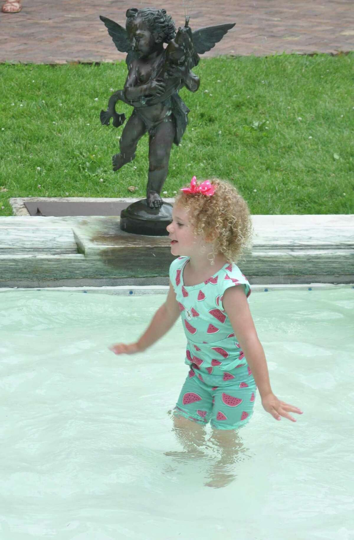Kelsey Finnneran plays in the fountain pool at Keeler Tavern Museum during the annual Watermelon Fest on July 4.
