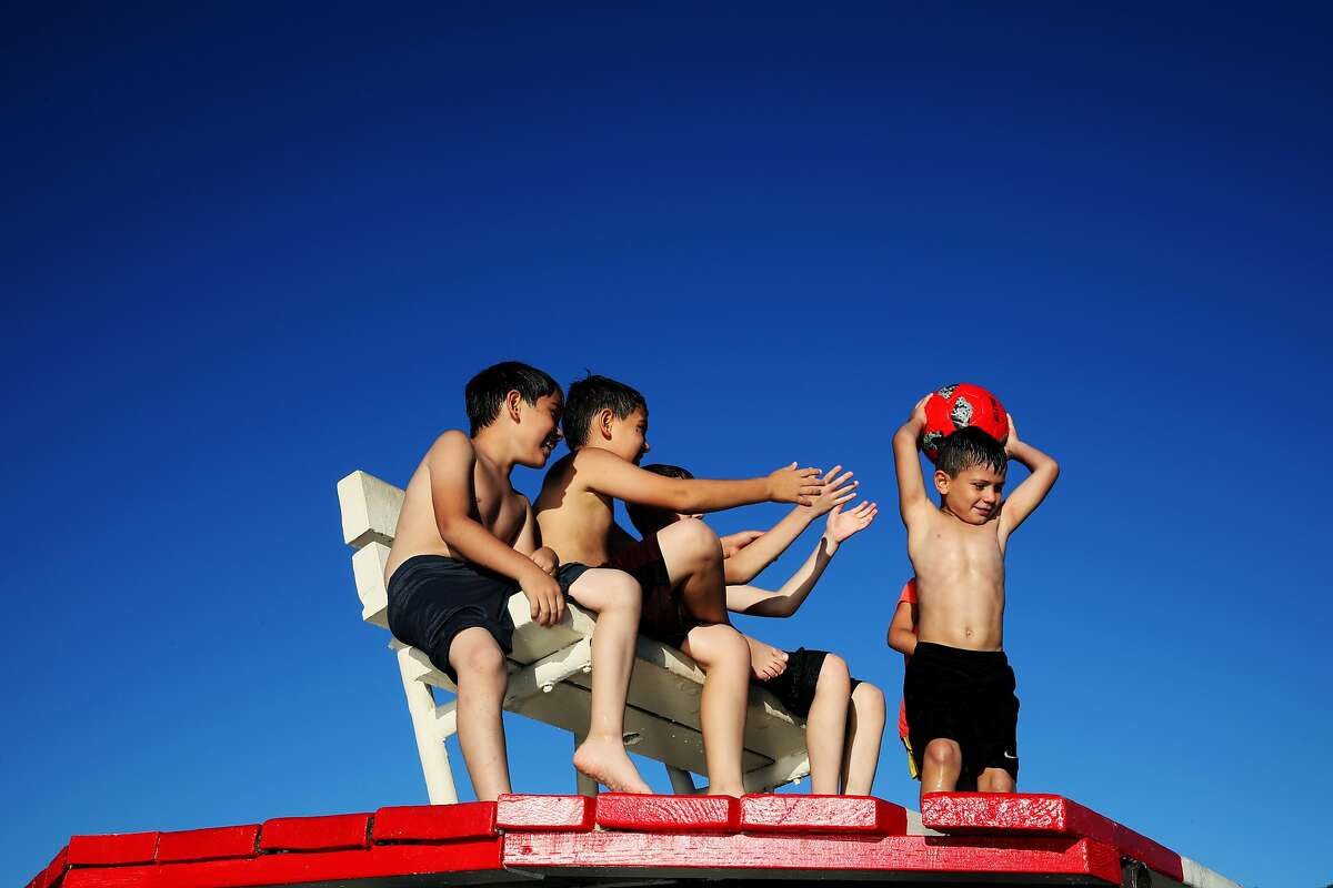 (From left to right): Alex Jauregui, 8, Christian Jauregui, 10, Gabriel Jauregil, 12, and Sherlyn Munoz, 7, watch Gael Ruano, 5, as he prepares to throw a ball as they hang out on a lifeguard stand at Del Valle Regional Park in Livermore, Calif., on Saturday, July 13, 2019. Rising temperatures are expected to make parts of the nation unlivable. A report due out Thursday by the Union of Concerned Scientists suggests that this warmer future is near. In one of the most comprehensive looks at where extreme heat will be most problematic in the U.S., and exactly when, the new study projects that cities in California's Central Valley will see weeks, if not months, of triple digit temperatures by 2050. San Francisco and other coastal cities will only see the occasional 100 degree day by mid-century, but not far inland, spots like Napa, Livermore and Morgan Hill will see triple digit weather as much as seven times more often.