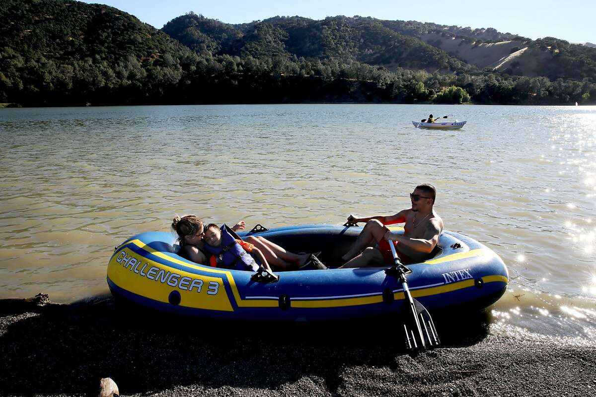 Maribel Cabrera, 31, holds Nicholas Allred, 8, the nephew of her boyfriend, David Wong, 29, as they prepare to boat in Lake del Valle at Del Valle Regional Park in Livermore, Calif., on Saturday, July 13, 2019. Rising temperatures are expected to make parts of the nation unlivable. A report due out Thursday by the Union of Concerned Scientists suggests that this warmer future is near. In one of the most comprehensive looks at where extreme heat will be most problematic in the U.S., and exactly when, the new study projects that cities in California's Central Valley will see weeks, if not months, of triple digit temperatures by 2050. San Francisco and other coastal cities will only see the occasional 100 degree day by mid-century, but not far inland, spots like Napa, Livermore and Morgan Hill will see triple digit weather as much as seven times more often.