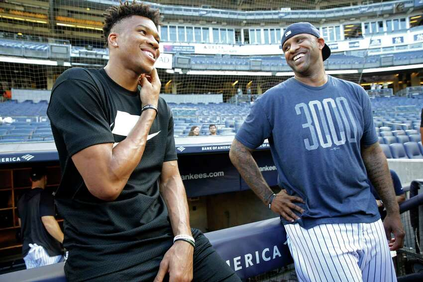 2019 NBA Most Valuable Player and Milwaukee Bucks forward Giannis Antetokounmpo, left, laughs with New York Yankees starting pitcher CC Sabathia before a baseball game between the Yankees and the Tampa Bay Rays, Monday, July 15, 2019, in New York. (AP Photo/Kathy Willens)